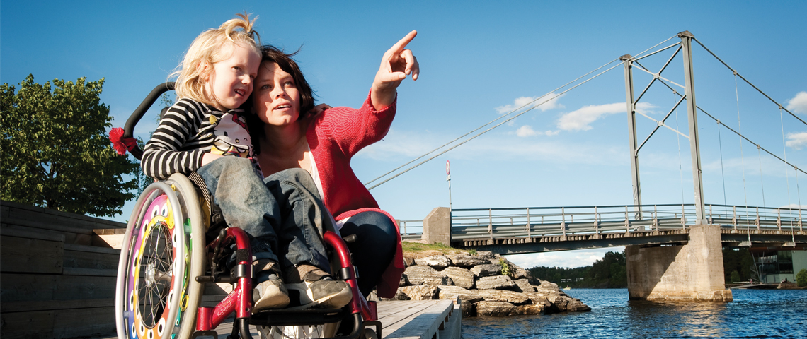 Mother together with daughter in a wheel chair by the sea